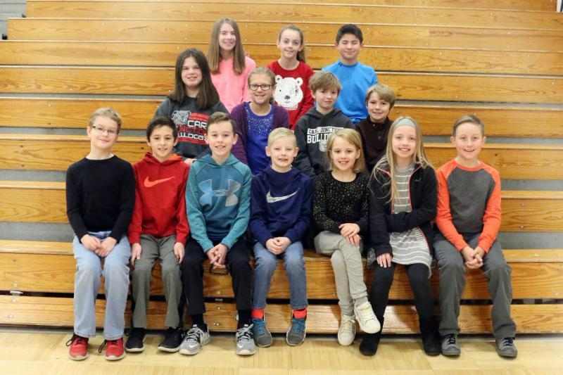 Fourteen intermediate students have qualified for the Regional Math tournament. They sit on gym bleachers smiling