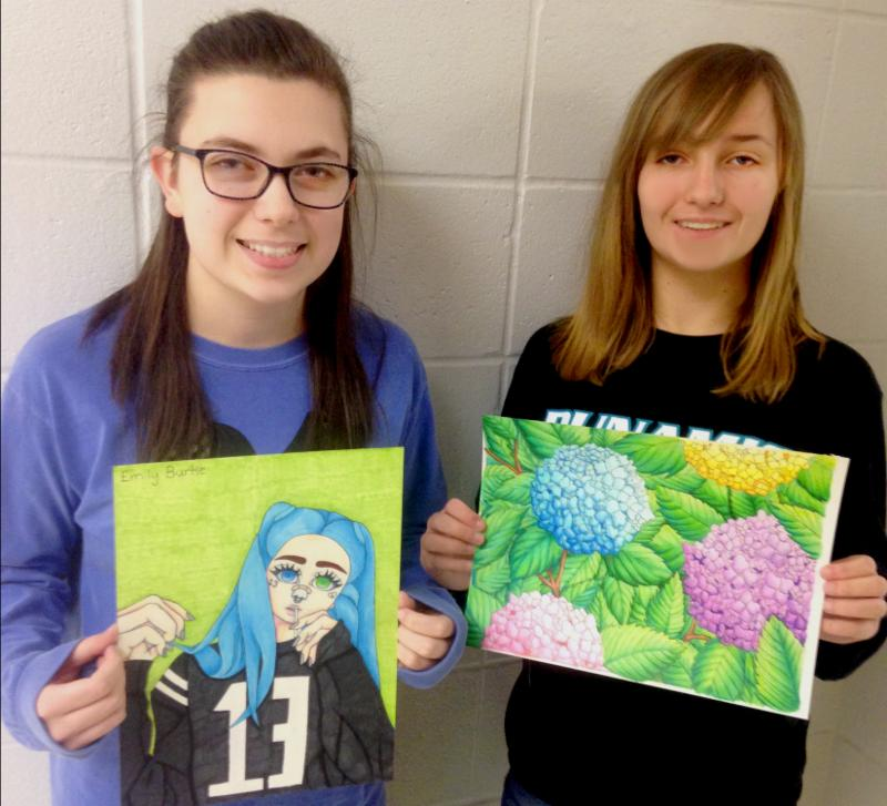 Two girls pose holding their art. One a portrait of a teen with blue hair and a jersey on, the other a drawing of hydrangea flowers