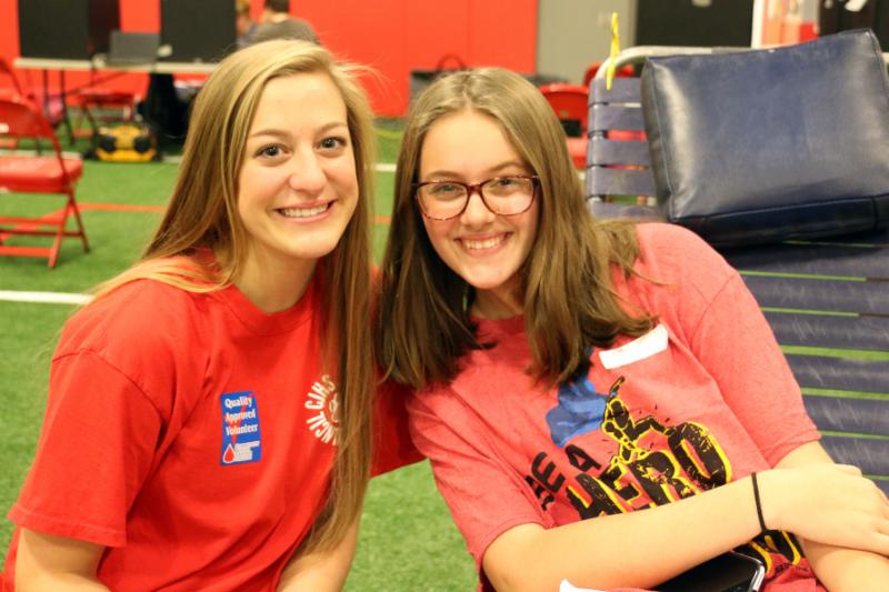 Two teen girls smile for the camera. One is kneeling on the ground, the other sits on a chair.