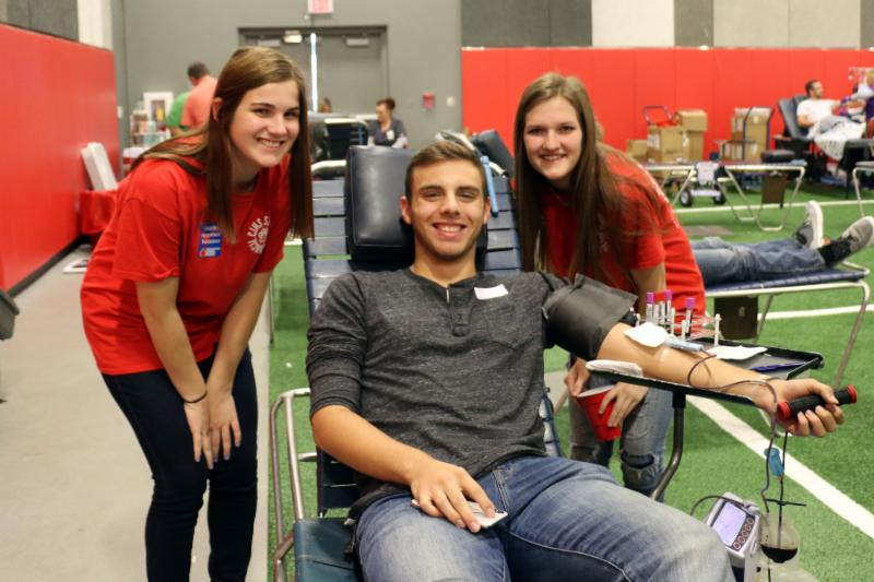 A young man lays on a chair getting his blood drawn. Two female students are standing on either side of him. All are smiling.