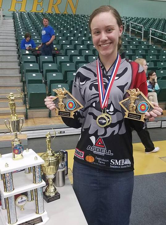 Frankie Goforth, a teen girl poses in a gym with medals and trophies. She has a bulldog archery shirt and long jean skirt on. Dark hair pulled back.