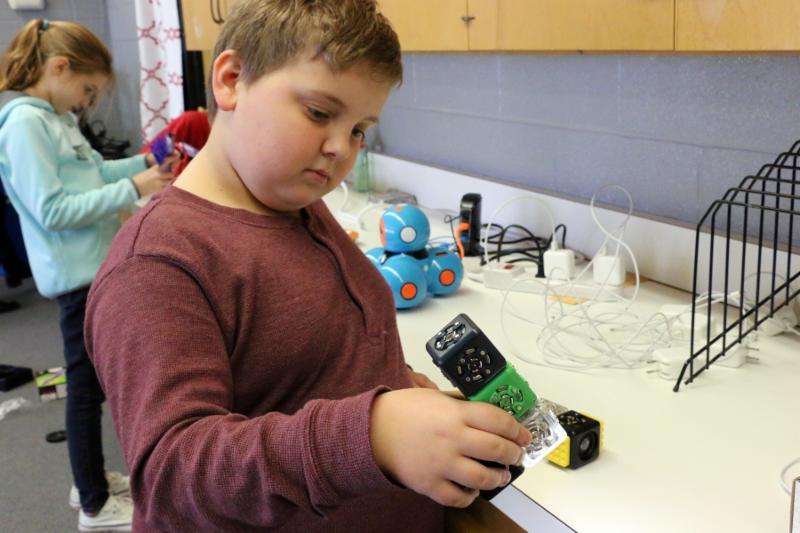 Young student Jakob McLeod holds and views three robotic cubes.