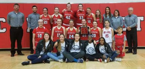 The Girls Basketball team poses in the gym in uniform with coaches and managers. The center player holds the CJ Classic plaque.