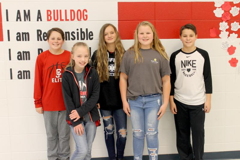A group of five fifth and sixth graders stand next to each other in the hallway, smiling