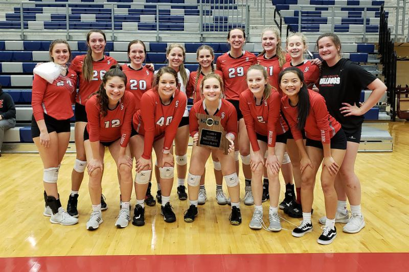 Group photo of the HS girls volleyball team holding their district plaque