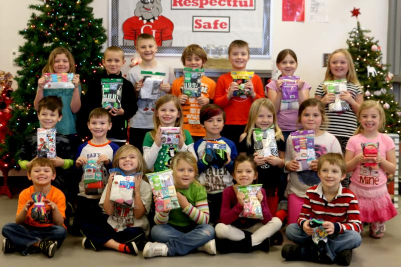 A group of K-1 students smile and hold up packages of underpants and socks from the 2016 drive.