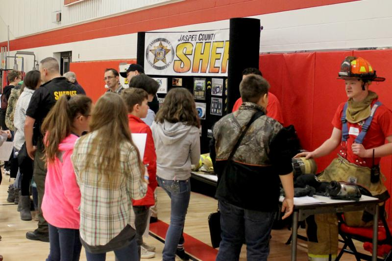 Representatives from the fire department and jasper county sheriff are in uniform behind information tables chatting with students gathered around