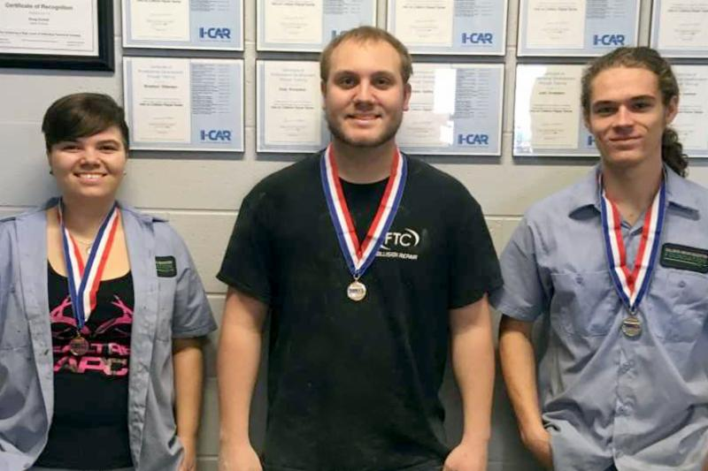 Students with medals around their neck posing in front of framed certificates. From left to right: Breana Miller, Ryan Allen, and Judd Donaldson