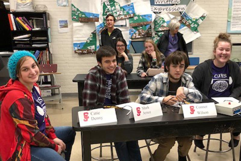 Scholar Bowl participants sit in desks in classroom setting