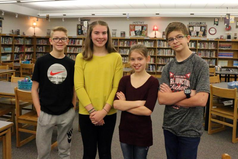 The four top spelling bee qualifiers stand in library