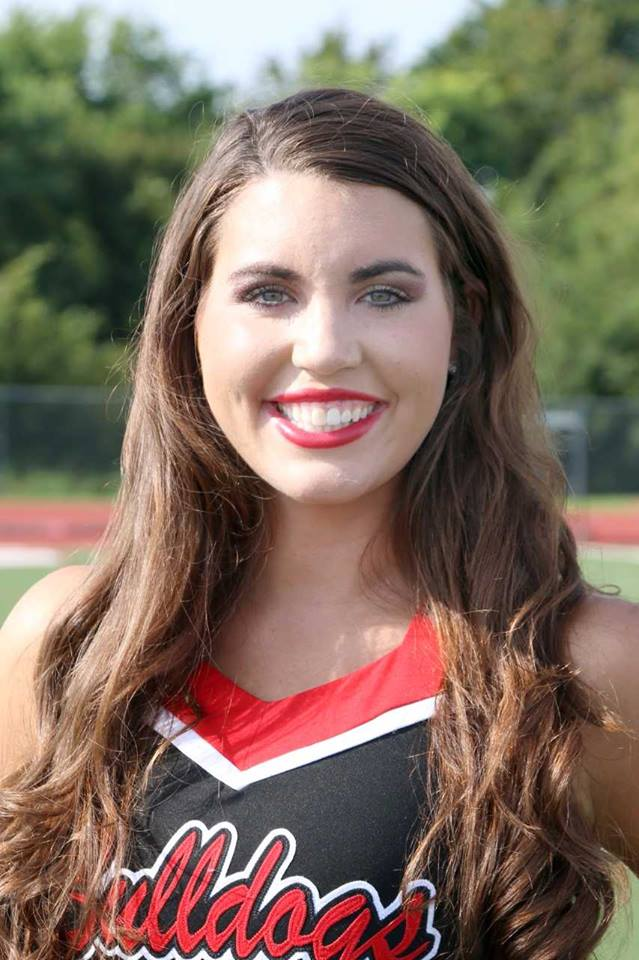 A headshot of CJHS Senior Paige Kalm in her dance team uniform. Football field in the background.