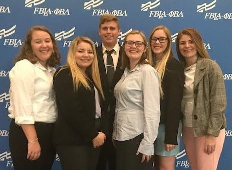 A group of Carl Junction high school students stand in front of a blue backdrop at FBLA's National Leadership Conference in Baltimore (L to R): Katie Crider, Josie Wilkins, Austin Rose, Anna Pence, Gracie Smith and Kayla Ellison