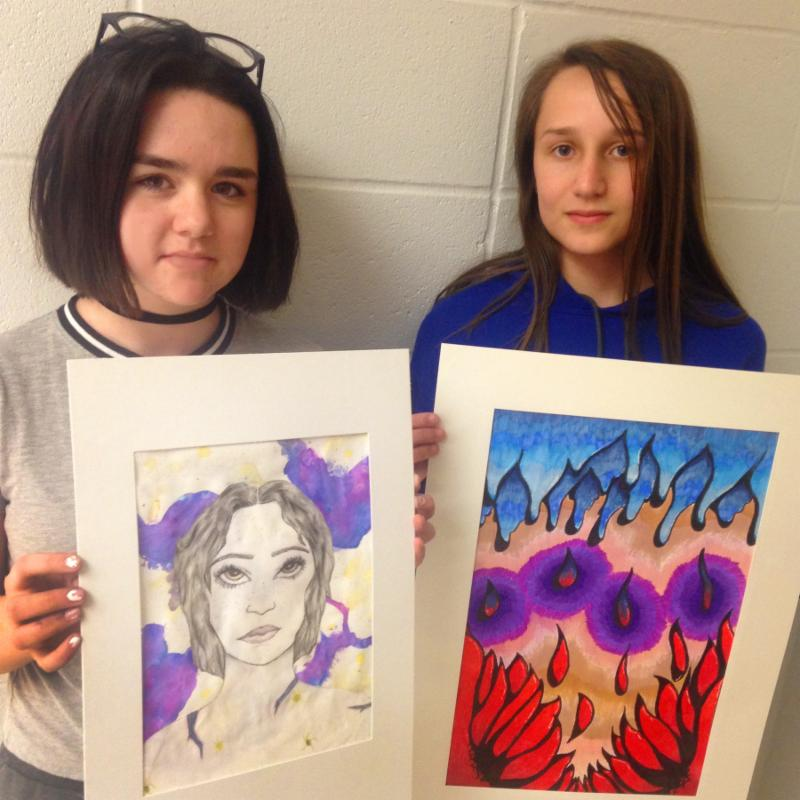 Girls pose with their art, one a portrait of a woman's head and shoulders the other an abstract scene with flower petals and icicles.