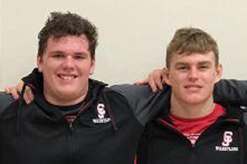 The two high school young men smile for the camera wearing their CJ Wrestling jackets.