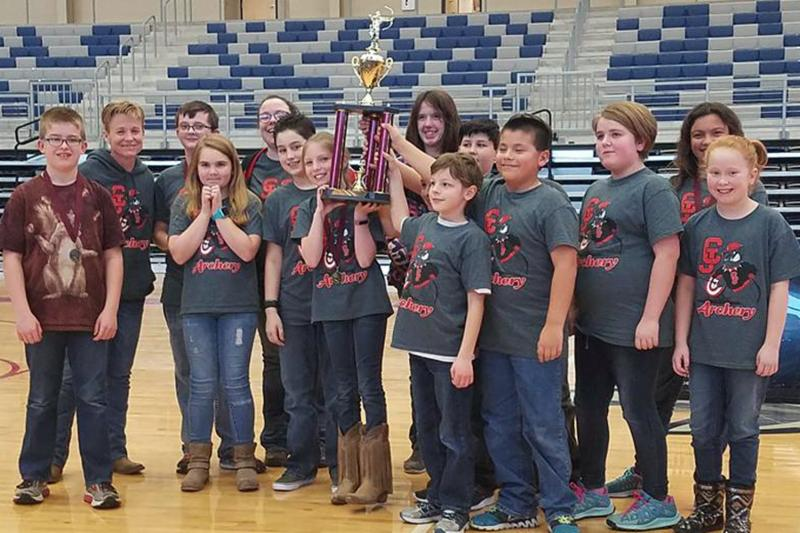 The elementary archery team stands in a gym with their archery t shirts on holding a trophy and smiling