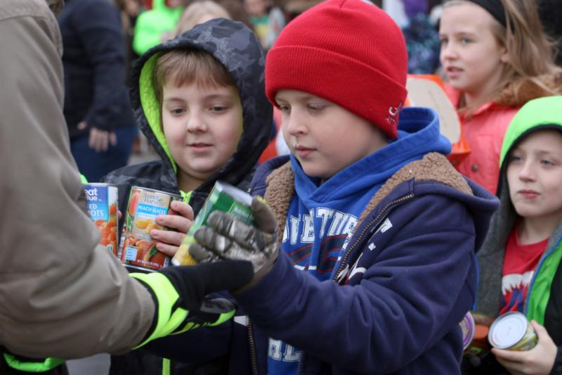 Two young boys wear warm winter clothes and hand canned goods to an adult with a firemans coat on.