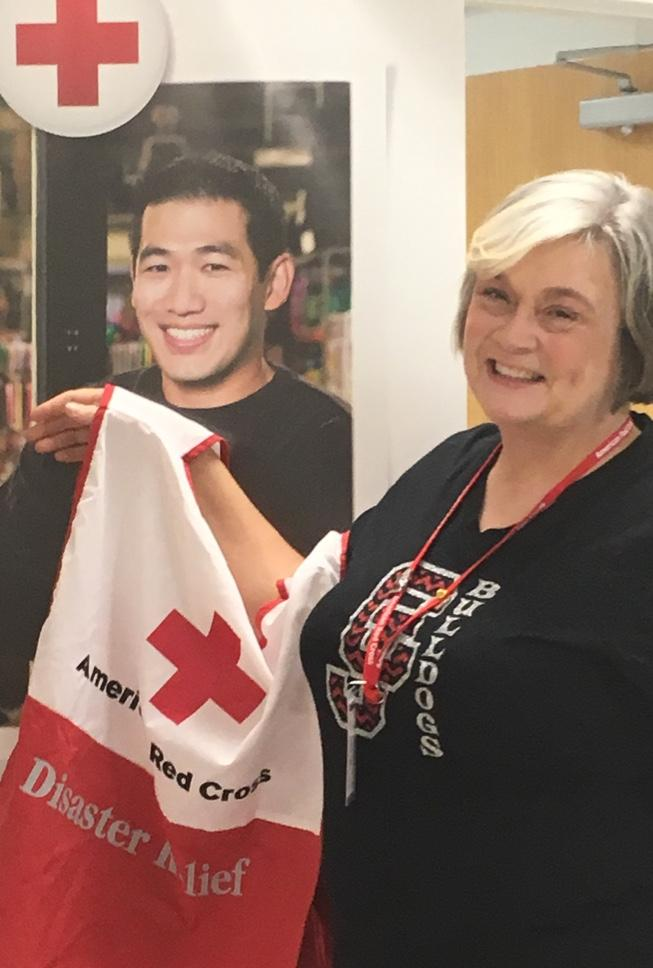 Counselor Lori Brock smiles in front of a red cross banner, holding a red cross disaster relief flag.