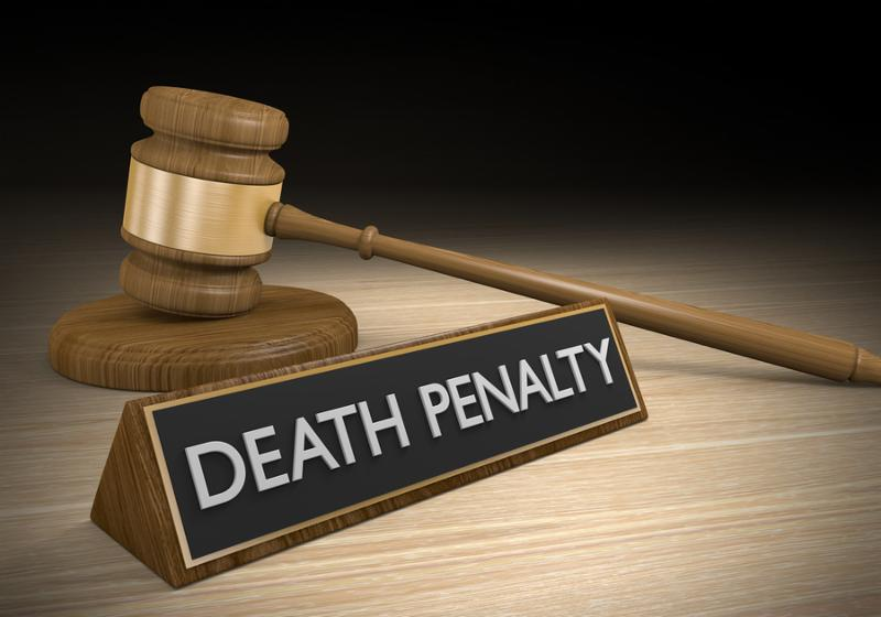 Capital punishment law concept of a wooden court gavel lying beside a sign that reads death penalty.
