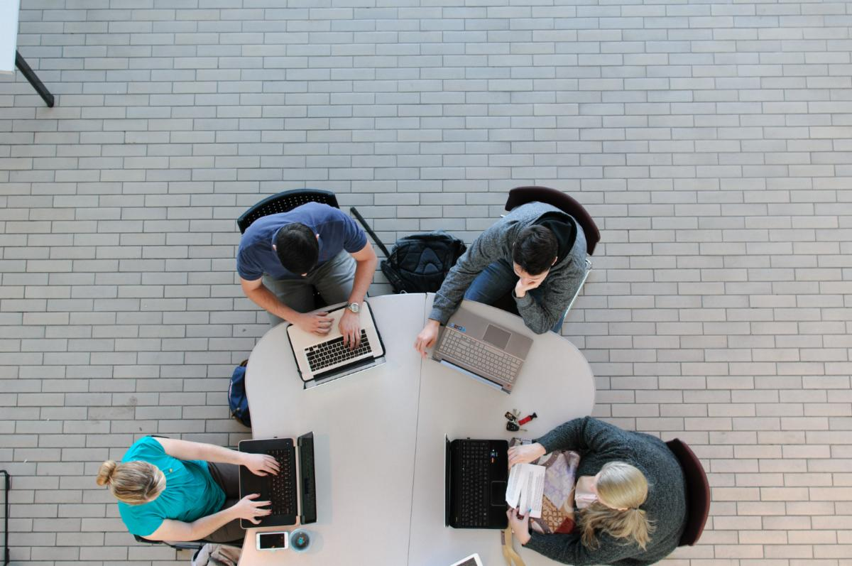 aerial view of four students working on their laptops at a table