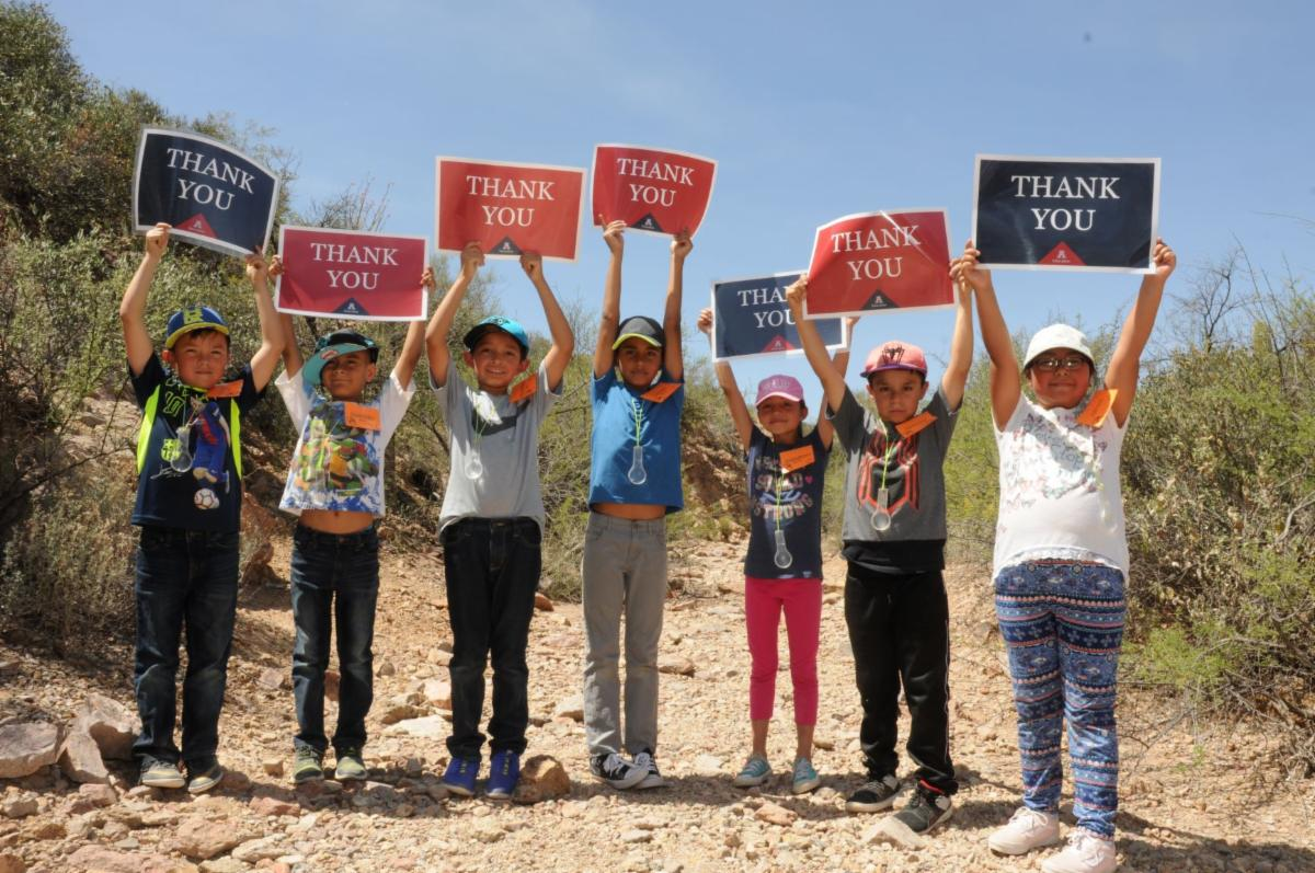 Photo has seven children in a desert landscape holding up Thank you signs