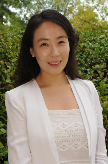 Sung Eun Jung is standing in front of a green bush wearing a white blouse and white blazer