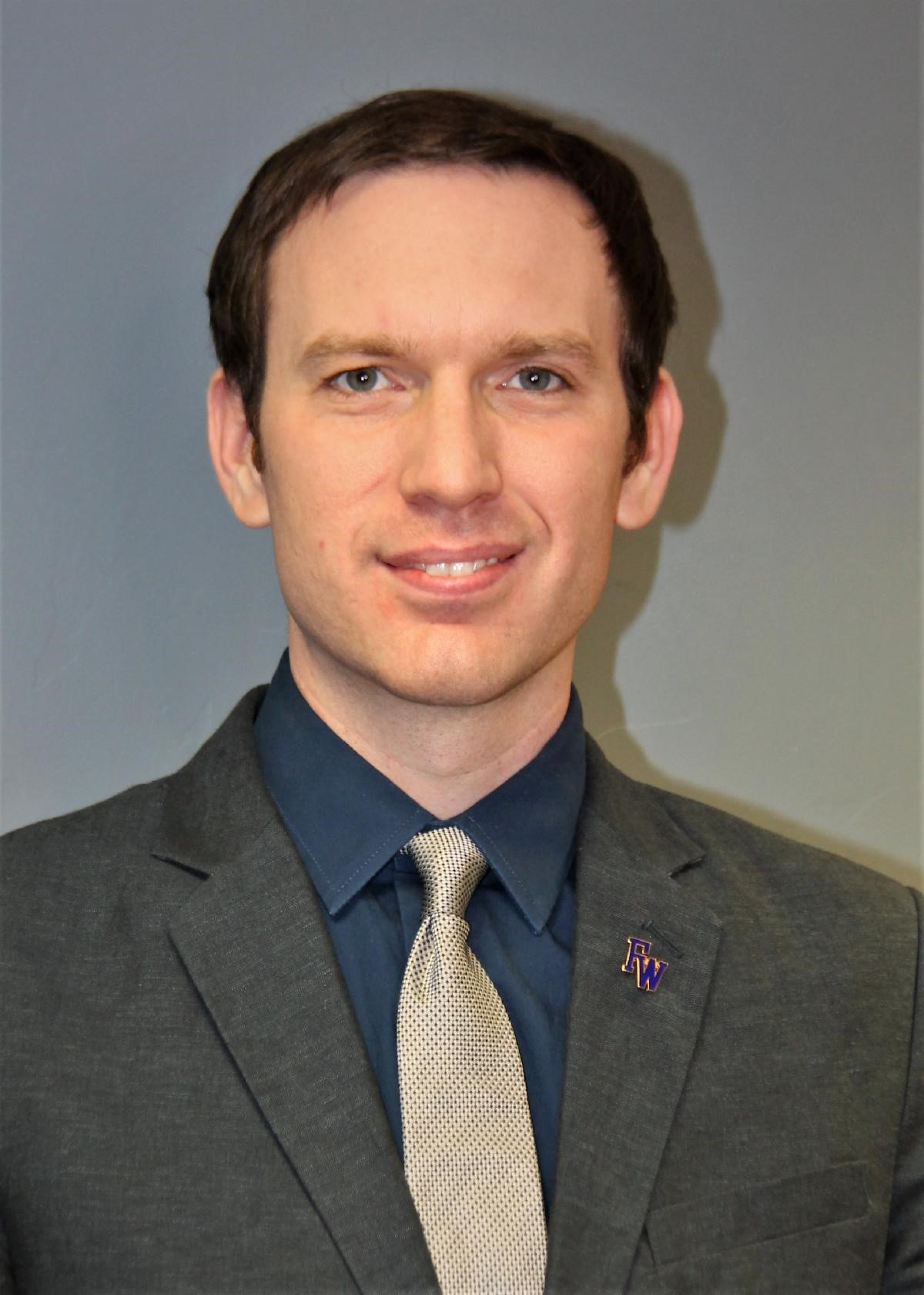 Chistopher Pankratz in suit and tie with Flowing Wells pin.
