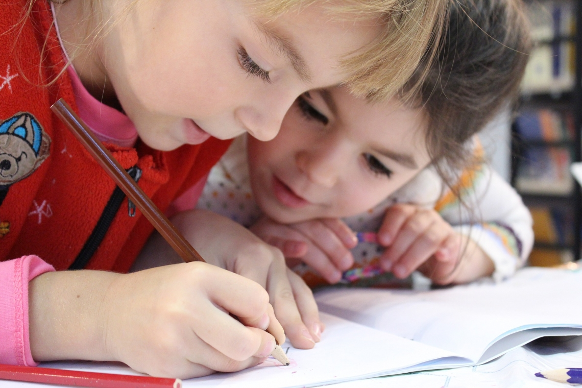 closeup of two young children writing
