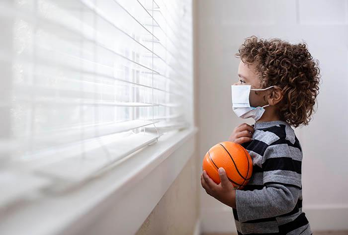 little boy with mask looking out window