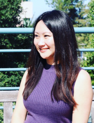 Photo of Katherine Cheng standing in front of trees and a handrail. She is wearing a purple blouse smiling and looking to the left.