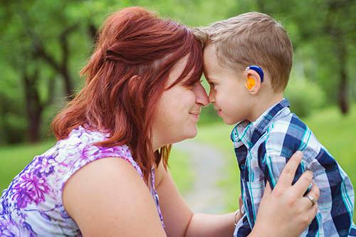woman hugging boy with hearing aids
