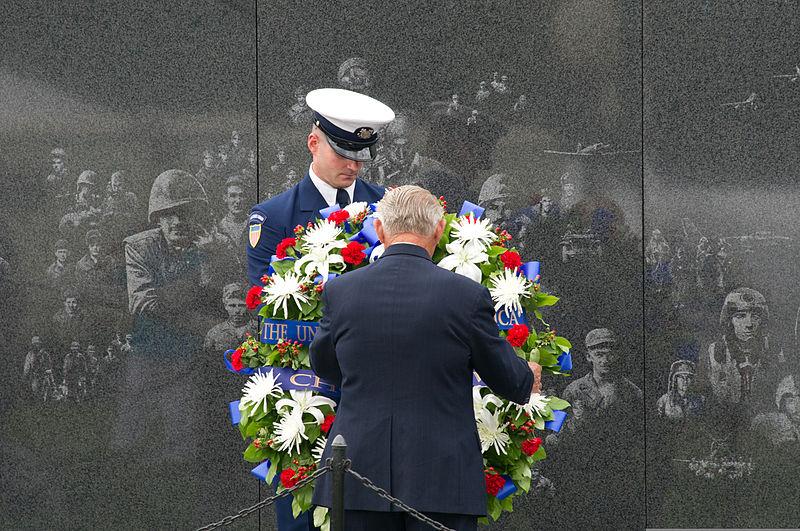 korean war veteran places wreath on memorial