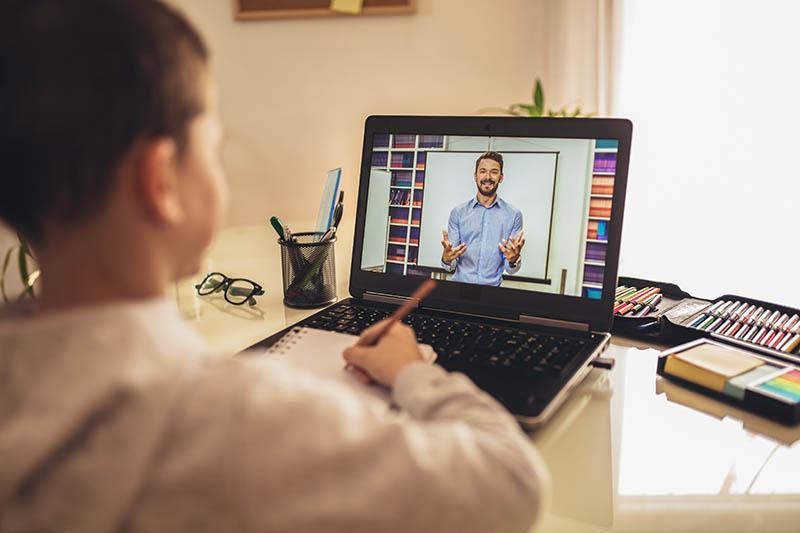boy working with online teacher