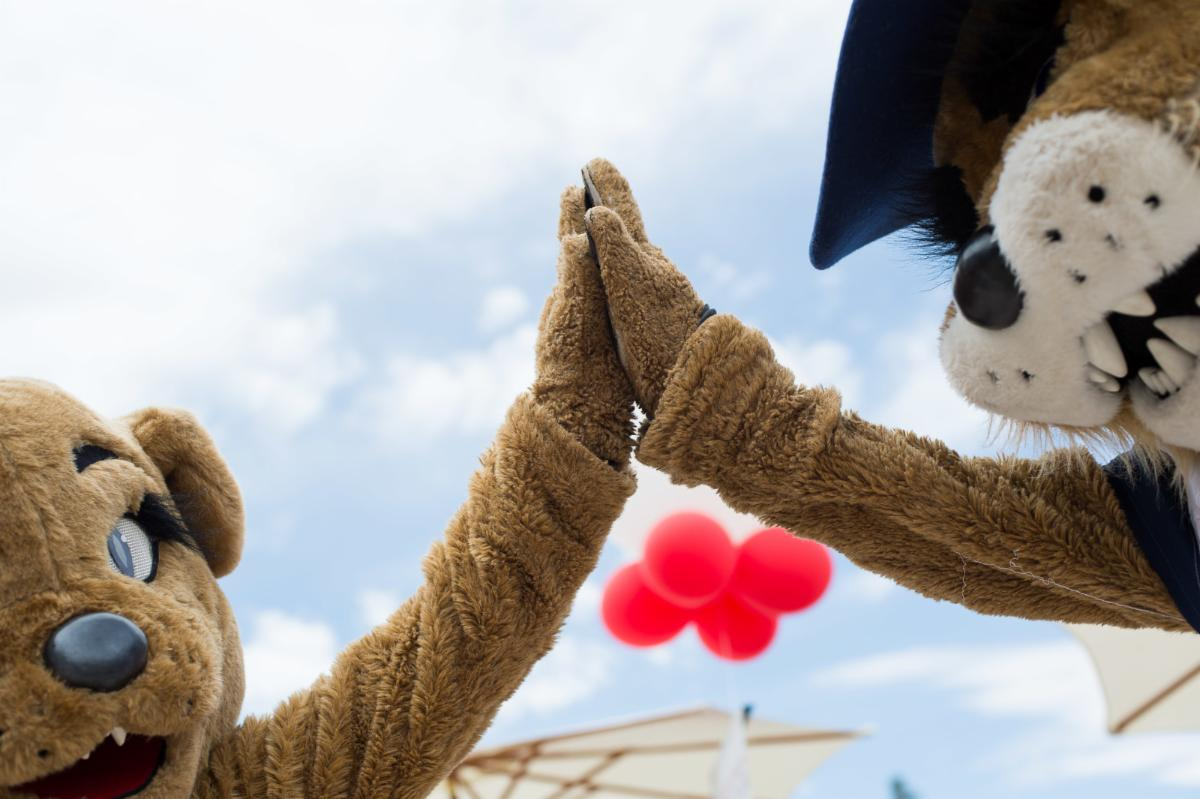 Wilma and Wilbur high fiving with red balloons in the background