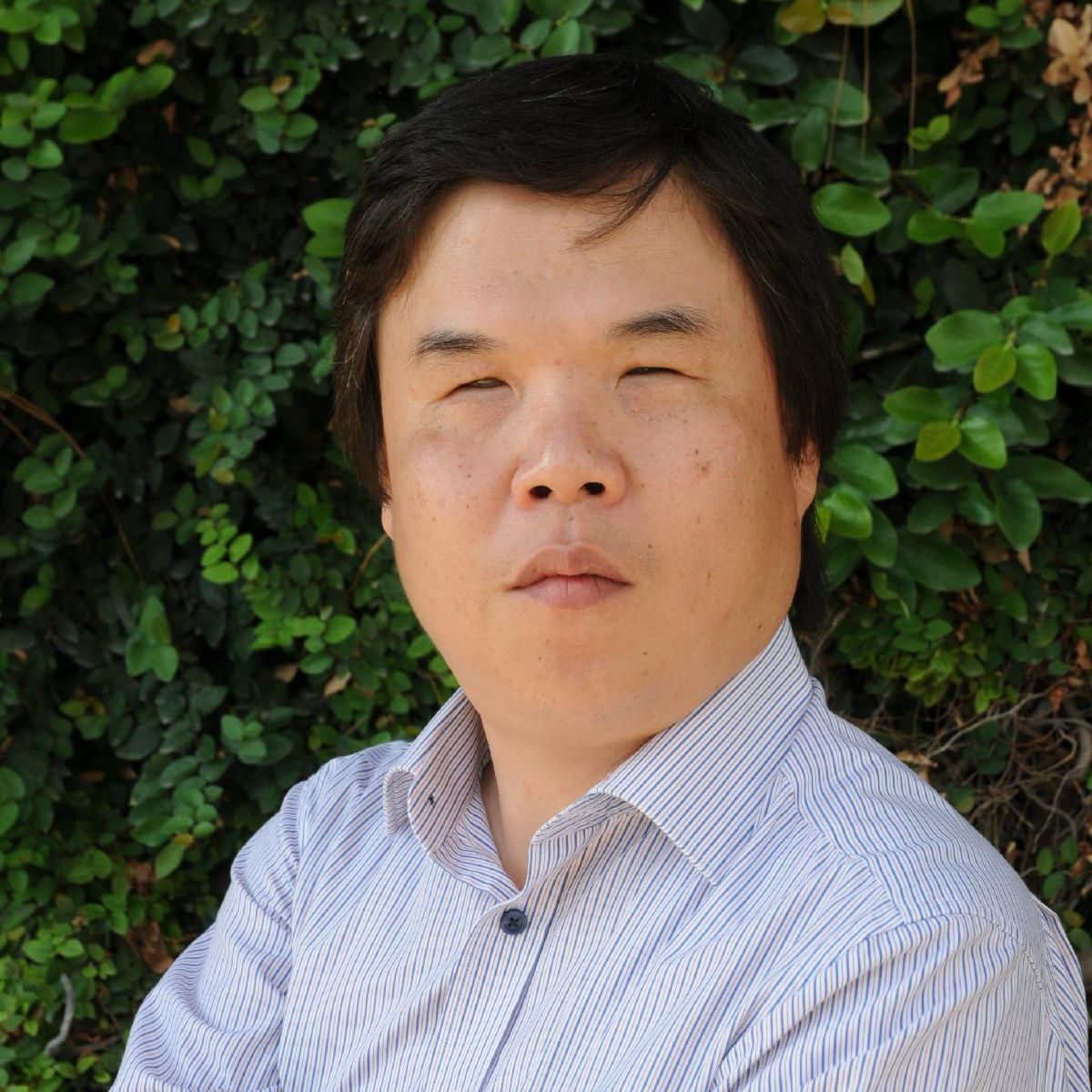 Photo of Professor Sunggye Hong in light blue button up collared shirt with arms crossed. Background is a tall green bush.