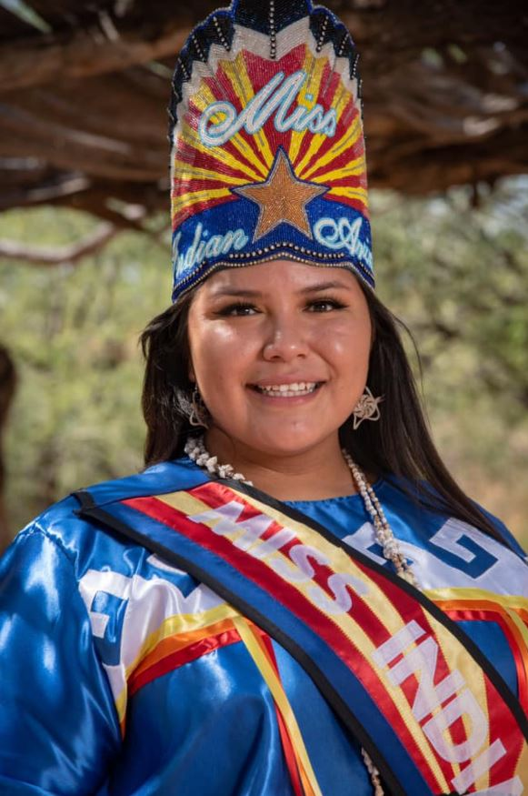 Amy Spotted Wolf wearing blue dress with red orange and yellow stripes and white pattern with a Miss Indian Arizona sash and crown on