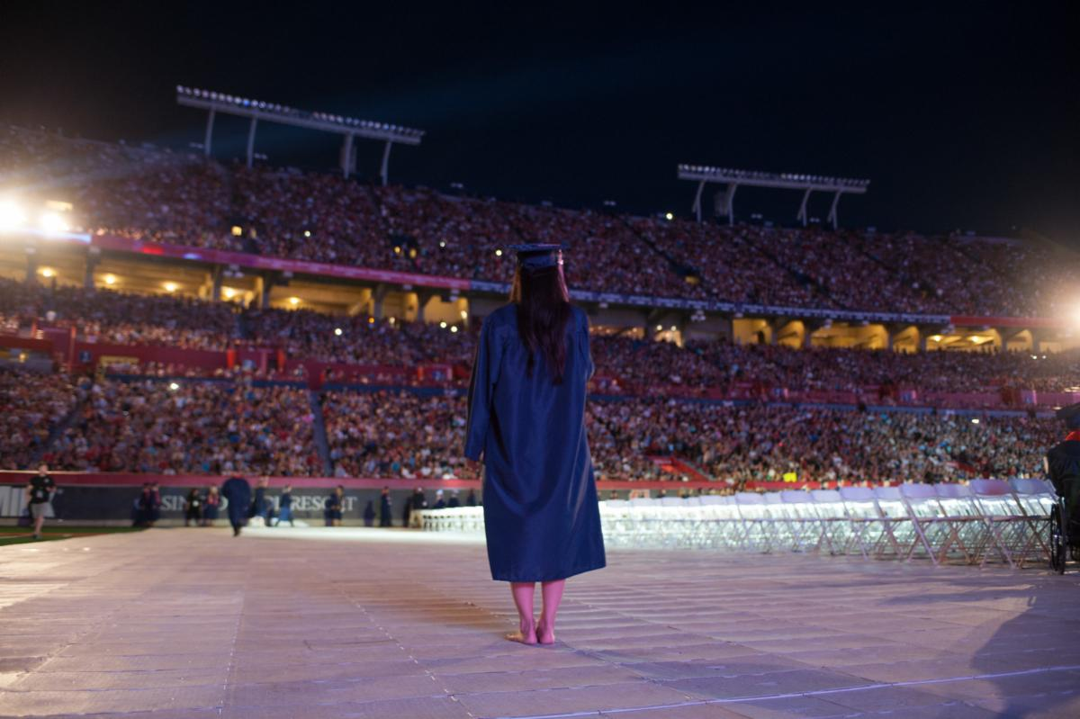 University of Arizona graduate walking in front of graduation audience
