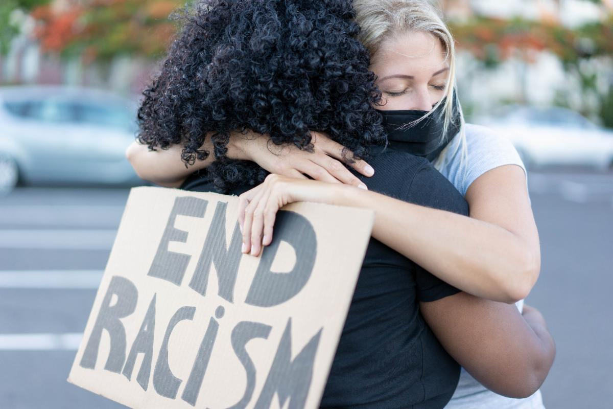 black and white women hugging with end racism sign