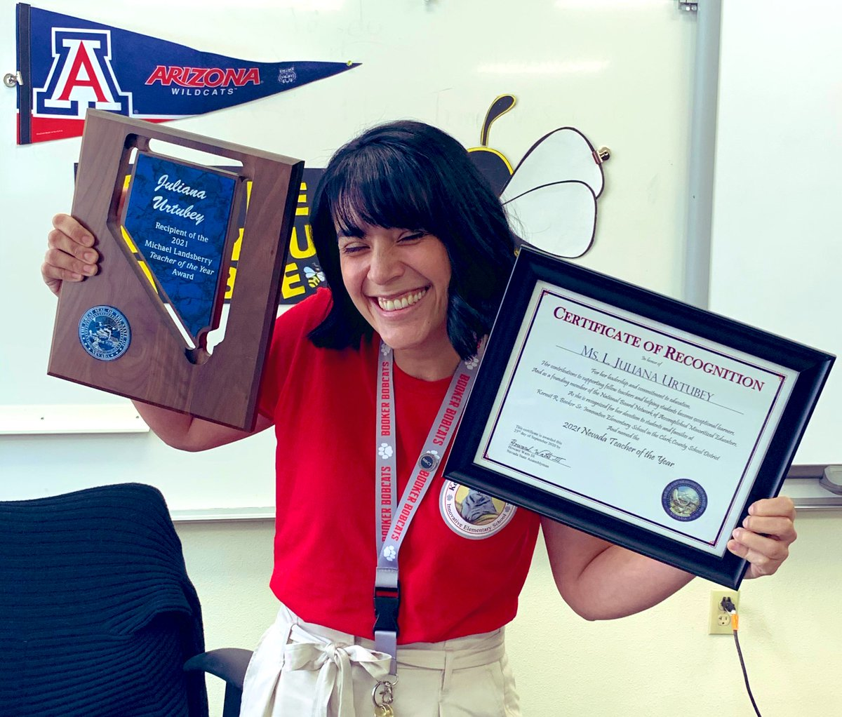 Photo of alumna Juliana Urtubey with her Nevada 2020 Teacher of the Year plaque and certificate. She is wearing a red tee and khaki shorts with a University of Arizona pendant flag in the background
