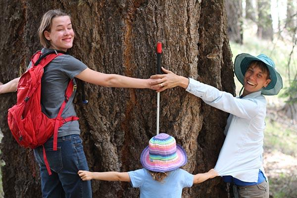 two women and child hugging tree