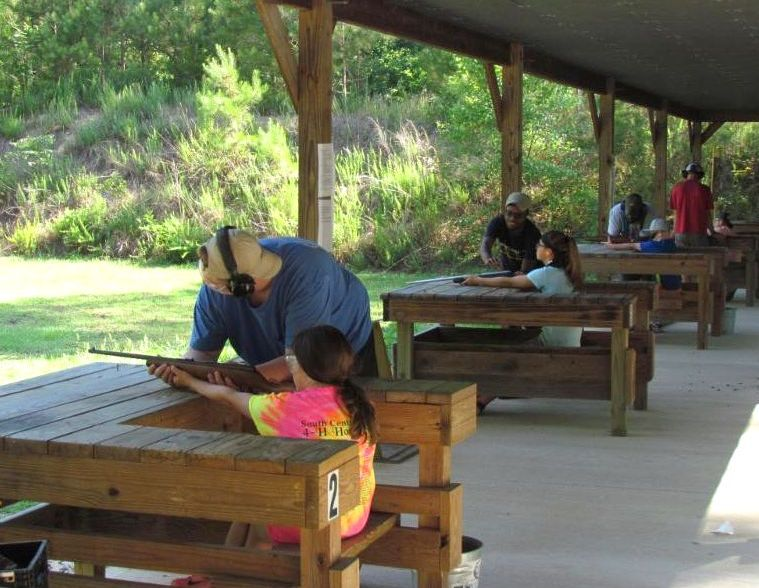 Camp members learning to shoot rifles