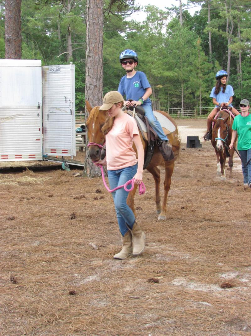4-H member riding a horse at camp