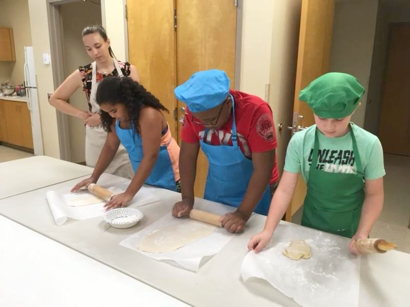 Camp participants rolling dough to make pasta