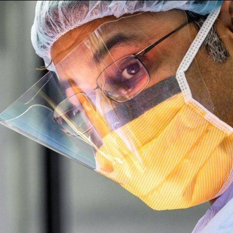 A surgeon in full equipment glancing up during a surgery