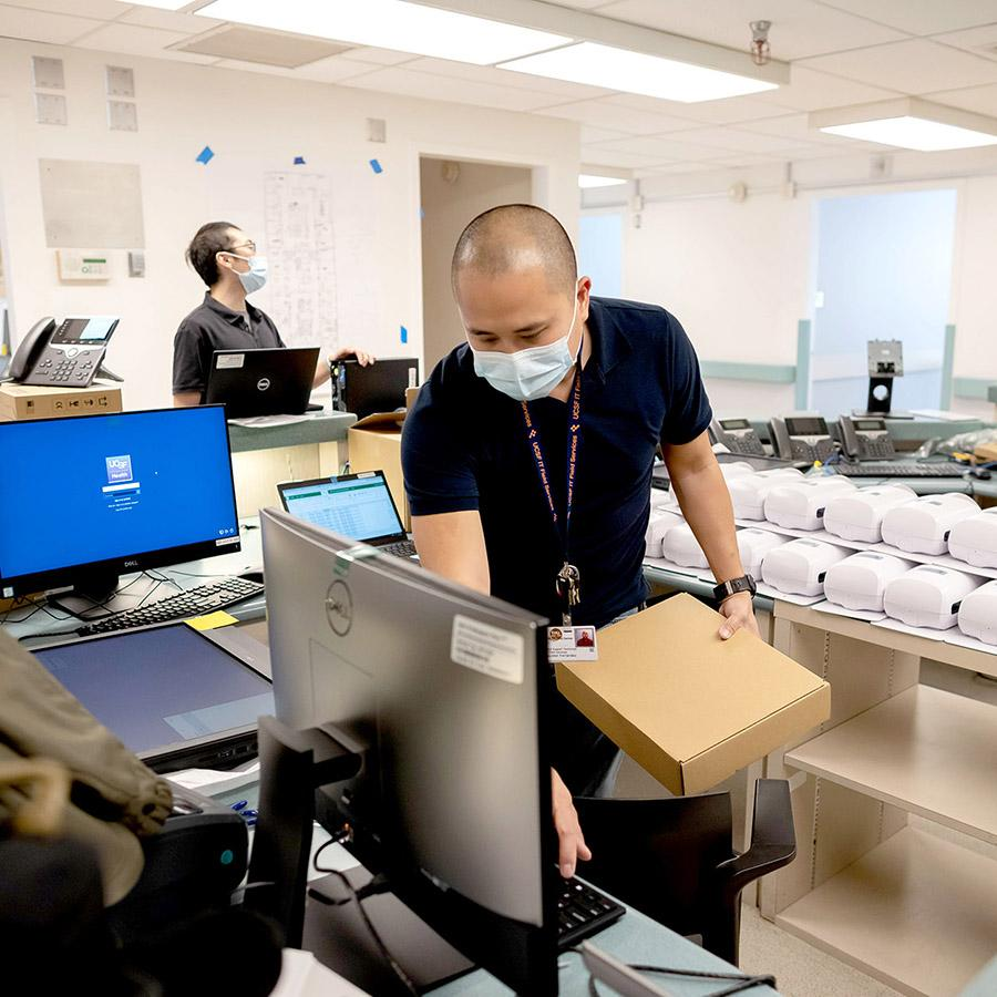 An IT worker wearing a mask checks a computer while holding a package