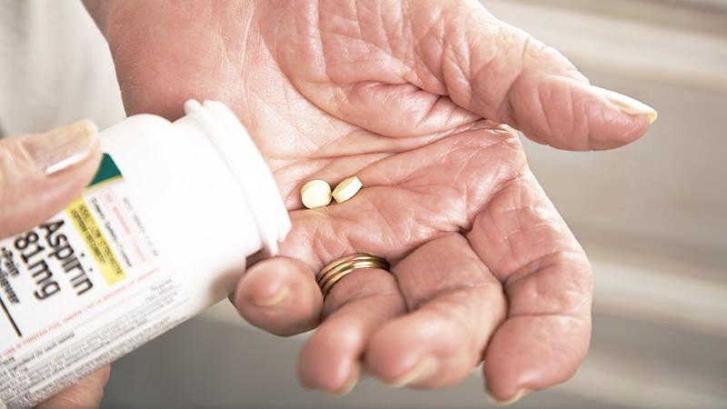 Aspirin pills in hand
