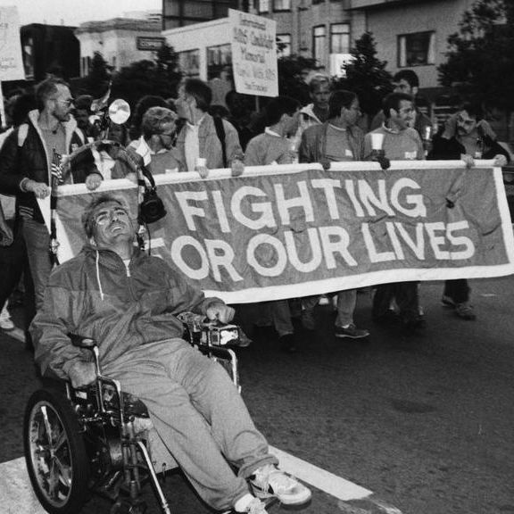 Gay men marching for their rights in the 80s with a banner that reads Fighting For Our Lives