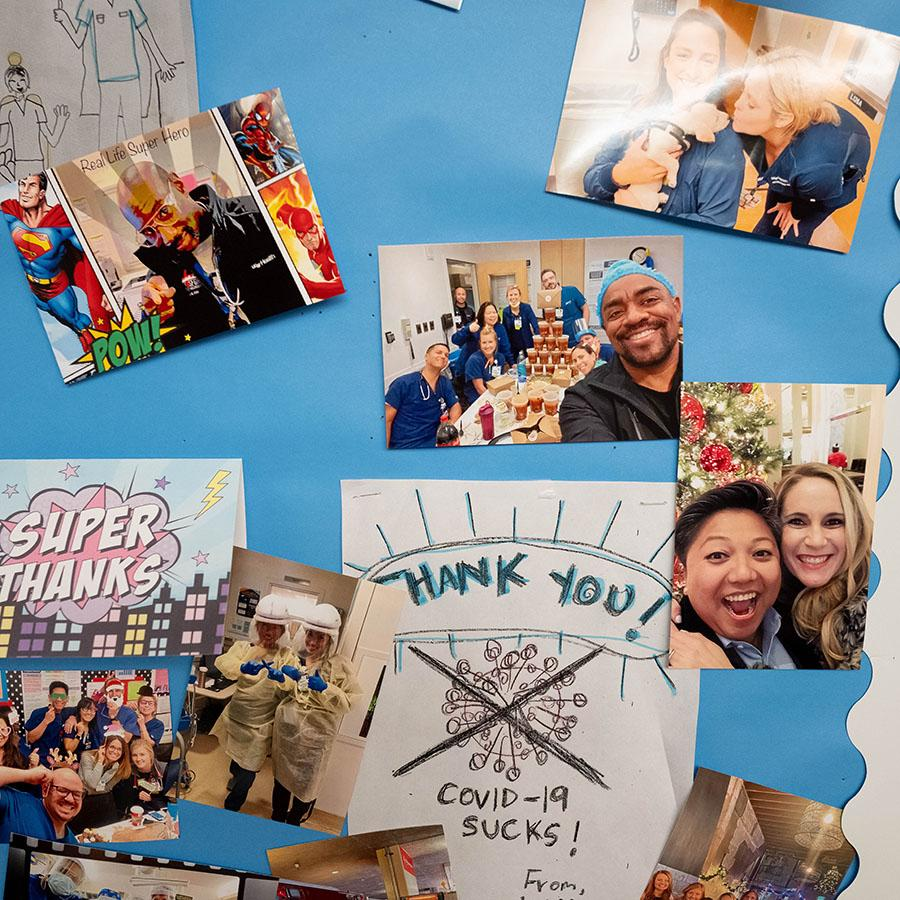 A board in a common area showing happy pictures of employees and thank you cards