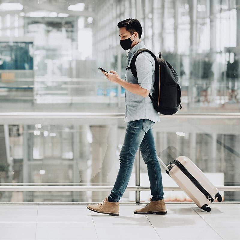 Man with luggage wearing a mask