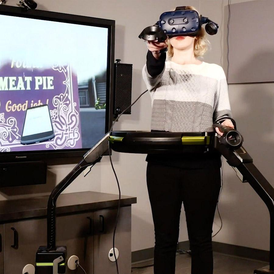 Woman wearing a VR headset handling a handle in front of her with a screen displaying the game she is exploring