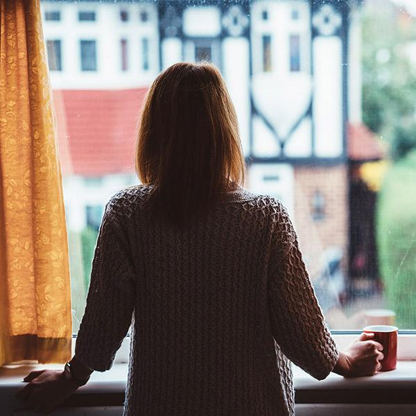 Woman stares out of a window